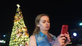 Mujer feliz en el fondo del árbol de navidad y de las palmeras en una ciudad tropical El concepto del viaje del Año Nuevo imagen de archivo libre de regalías