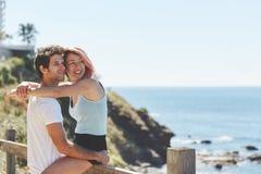 Mujer feliz en el novio de abarcamiento de la cerca que mira lejos Foto de archivo
