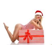 Mujer feliz en el sombrero de Papá Noel de la Navidad con la actual sonrisa grande del regalo Foto de archivo