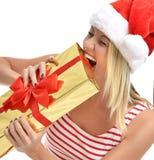 Mujer feliz en el sombrero de Papá Noel de la Navidad que intenta morder el actual regalo e Fotos de archivo libres de regalías