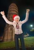 Mujer feliz en el sombrero de Papá Noel que disfruta cerca de la torre inclinada de Pisa Fotografía de archivo