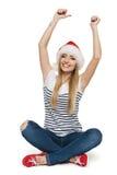 Mujer feliz en el sombrero de Santa con los brazos aumentados Fotografía de archivo