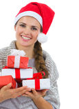 Mujer feliz en el sombrero de Santa con los rectángulos de regalo de la Navidad Foto de archivo