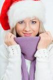 Mujer feliz en el sombrero de santa que se sienta cerca del sofá Imagen de archivo libre de regalías