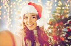 Mujer feliz en el sombrero de santa sobre el árbol de navidad Imagen de archivo libre de regalías