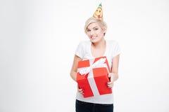 Mujer feliz en el sombrero del partido que sostiene la caja de regalo Fotos de archivo