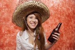 Mujer feliz en el sombrero mexicano que sostiene la botella de cerveza en restaurante Fotos de archivo