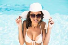 Mujer feliz en el sombrero que se divierte por el lado de la piscina Fotos de archivo libres de regalías