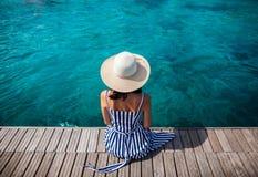 Mujer feliz en el sombrero que se relaja en el embarcadero del mar en la isla de Cerdeña, Italia imágenes de archivo libres de regalías