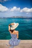 Mujer feliz en el sombrero que se relaja en el embarcadero del mar en la isla de Cerdeña, Italia foto de archivo libre de regalías