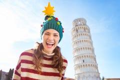 Mujer feliz en el viaje que se inclina cercano del sombrero del árbol de navidad de Pisa Imagen de archivo libre de regalías