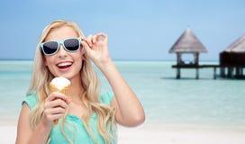 Mujer feliz en gafas de sol con helado en la playa Foto de archivo
