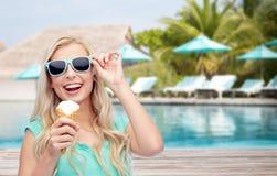 Mujer feliz en gafas de sol con helado en la playa Imagen de archivo