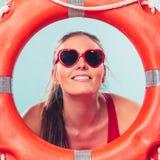 Mujer feliz en gafas de sol con salvavidas de la boya de anillo Foto de archivo