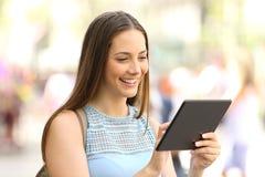 Mujer feliz en línea con una tableta en la calle Imagenes de archivo