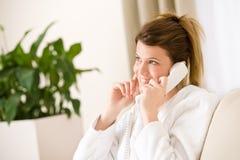 Mujer feliz en la albornoz blanca con el hogar del teléfono Fotos de archivo libres de regalías