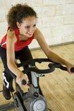 Mujer feliz en la bici de ejercicio Imagen de archivo