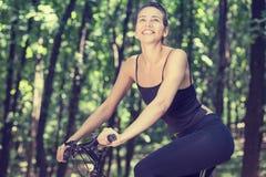 Mujer feliz en la bici que se coloca en un camino de la colina que disfruta de día soleado hermoso del verano fotos de archivo