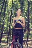 Mujer feliz en la bici que se coloca en un camino de la colina que disfruta de v hermoso fotografía de archivo