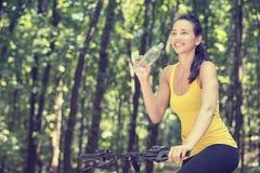 Mujer feliz en la bici que se coloca en un camino de la colina que disfruta de v hermoso imagen de archivo