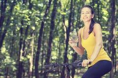 Mujer feliz en la bici que se coloca en un camino de la colina que disfruta de v hermoso imagen de archivo libre de regalías