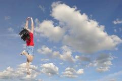 Mujer feliz en la camiseta roja que salta al cielo azul del clound Fotos de archivo