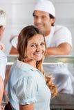 Mujer feliz en la carnicería imagen de archivo