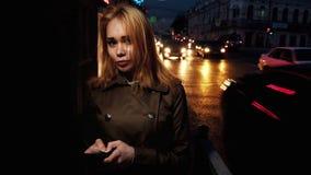 Mujer feliz en la ciudad por la tarde, coches móviles en el fondo, tiro entonado almacen de video