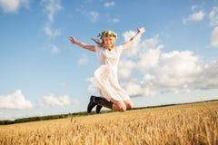 Mujer feliz en la guirnalda que salta en campo de cereal Fotos de archivo