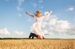 Mujer feliz en la guirnalda que salta en campo de cereal Foto de archivo