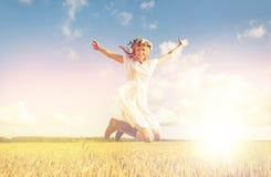 Mujer feliz en la guirnalda que salta en campo de cereal Imágenes de archivo libres de regalías
