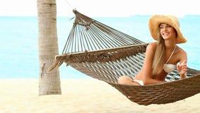 Mujer feliz en la hamaca en la playa exótica almacen de video