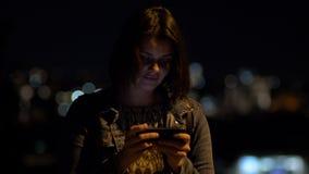 Mujer feliz en la noche en mensaje que manda un SMS de la ciudad con el teléfono celular metrajes