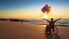 Mujer feliz en la playa que lleva a cabo impulsos metrajes