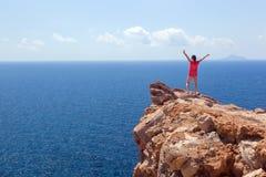 Mujer feliz en la roca con las manos para arriba Ganador, éxito, viaje imagen de archivo