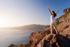 Mujer feliz en la roca con las manos para arriba Santorini Imágenes de archivo libres de regalías