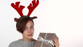 Mujer feliz en la venda de las astas del reno que mira su regalo de Navidad metrajes