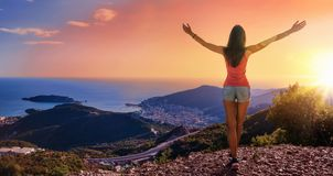 Mujer feliz en las montañas que miran la puesta del sol fotos de archivo libres de regalías