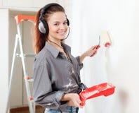 Mujer feliz en las pinturas de los auriculares wal Foto de archivo