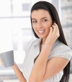 Mujer feliz en llamada de teléfono con café Fotografía de archivo