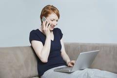 Mujer feliz en llamada mientras que usa el ordenador portátil Foto de archivo