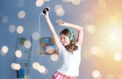 Mujer feliz en los auriculares ihaving la diversión en casa Fotos de archivo libres de regalías