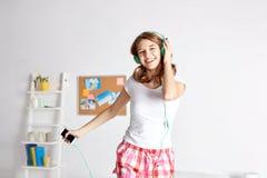 Mujer feliz en los auriculares ihaving la diversión en casa Imagenes de archivo