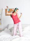 Mujer feliz en los auriculares ihaving la diversión en casa Fotos de archivo
