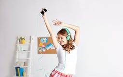 Mujer feliz en los auriculares ihaving la diversión en casa Foto de archivo libre de regalías