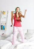 Mujer feliz en los auriculares ihaving la diversión en casa Fotografía de archivo libre de regalías