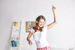 Mujer feliz en los auriculares ihaving la diversión en casa Imagen de archivo