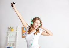 Mujer feliz en los auriculares ihaving la diversión en casa Foto de archivo
