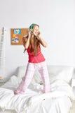 Mujer feliz en los auriculares ihaving la diversión en casa Fotografía de archivo