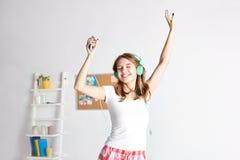 Mujer feliz en los auriculares ihaving la diversión en casa Imagen de archivo libre de regalías